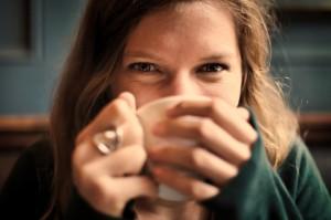 Private Krankenversicherung für Studenten unter bestimmten Voraussetzungen möglich - Studentin lächelt und trinkt Kaffee