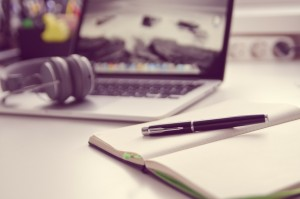PKV Fristen für Studenten besonders wichtig - Schreibtisch mit Laptop, Füller und Kopfhörern